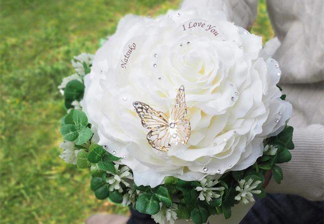 クローバーの輪で囲まれた白いバラのブーケ
