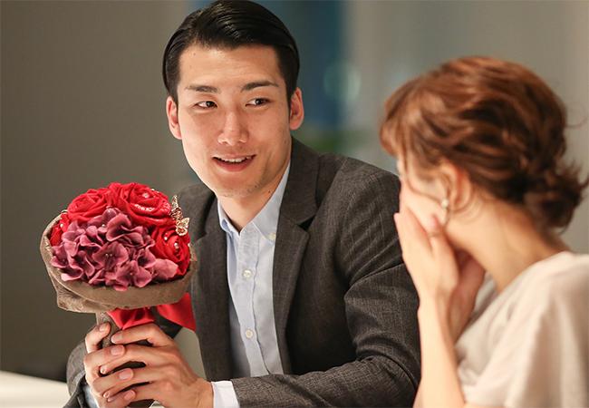 バーで赤バラの花束を渡してプロポーズ