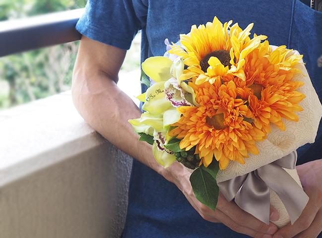 ひまわりの花束を持つ男性