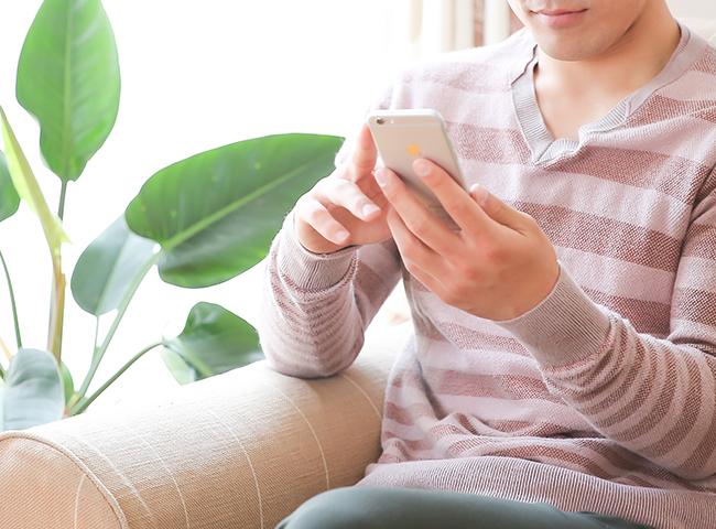 スマートフォンで調べ物をする男性
