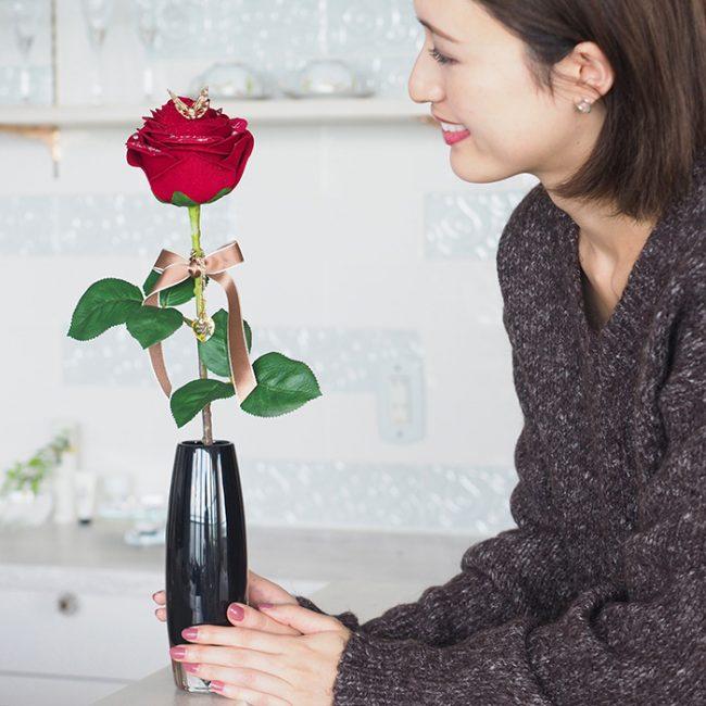 枯れないバラを見つめる彼女