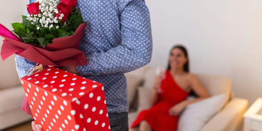 バラとプレゼントを渡す男性